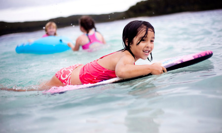 Little girl surfing on Guam