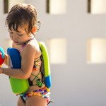 Baby girl at swimming pool with watering can