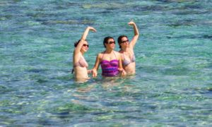 Three Asian women swimming in Tumon Bay, Guam