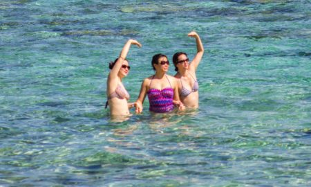 Three Asian women swimming in Tumon Bay, Guam